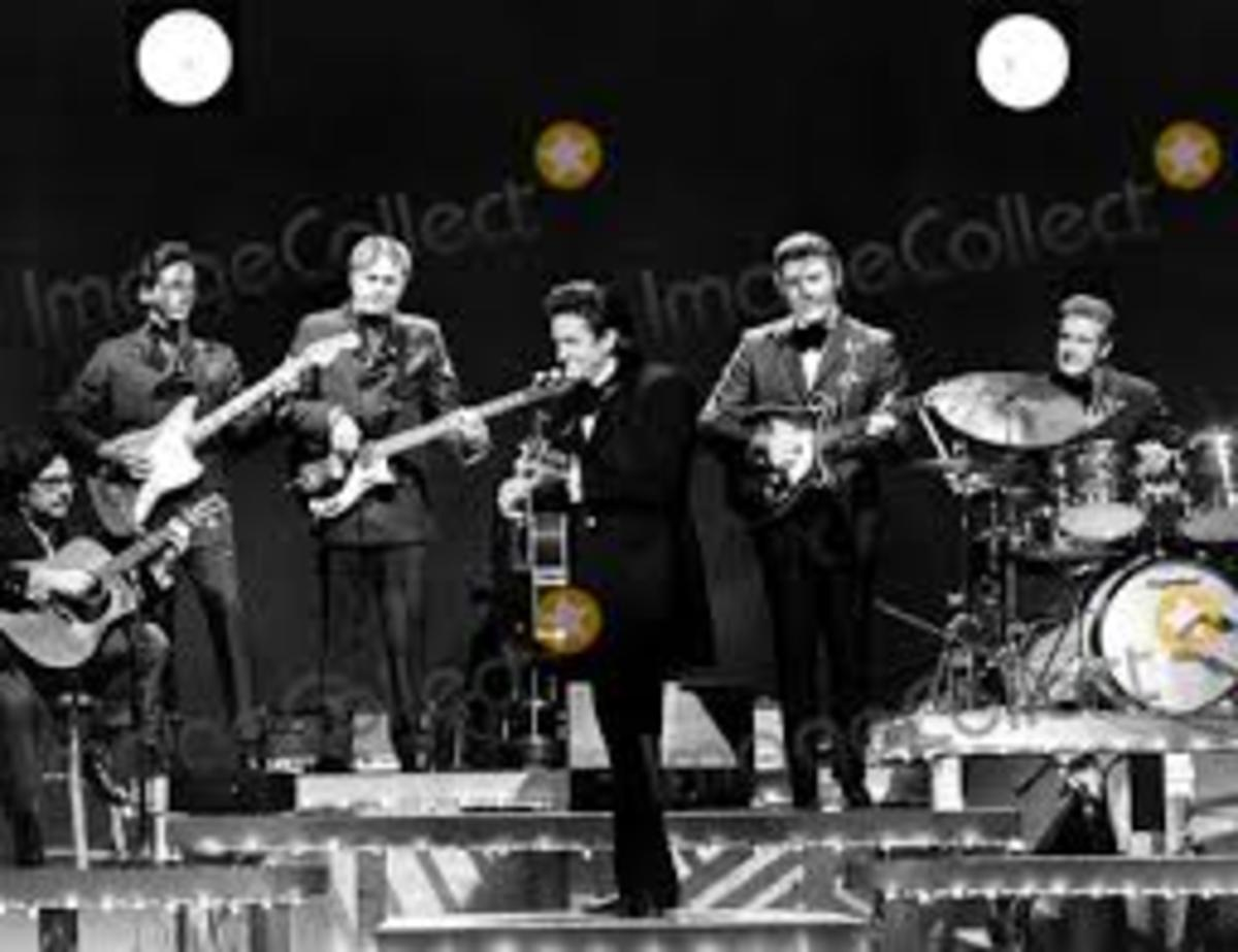 Norman Blake, at far left, and seated, on stage with Johnny Cash.