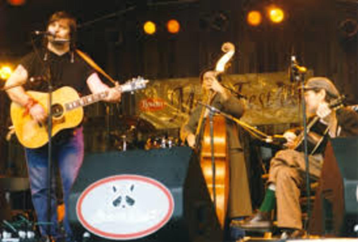 Steve Earle standing at far left, with Norman Blake, seated at far right, at the North Carolina Merlefest festival in the late 1990s.