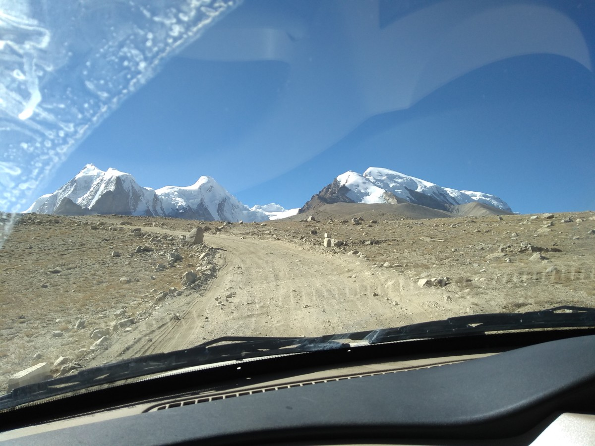 Blue sky, snow-capped mountains, lonely road, and us