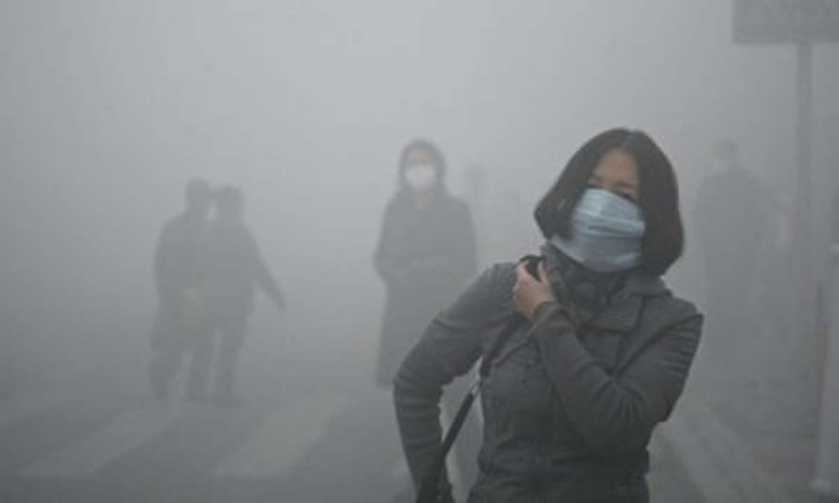 Citizens walking through smog in Beijing
