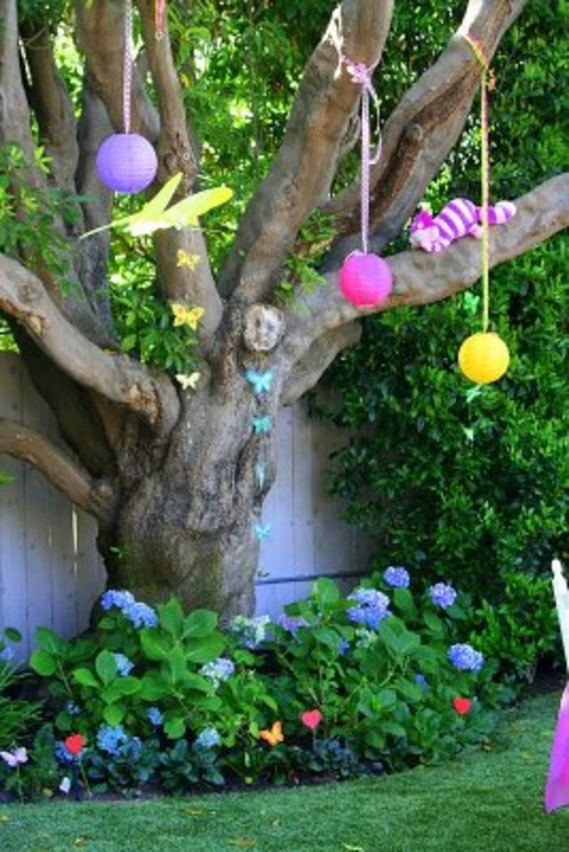 Paper lanterns and a Cheshire cat decorate this tree, found at http://partywishesscv.blogspot.com/2009/07/mad-hatter-tea-party.html