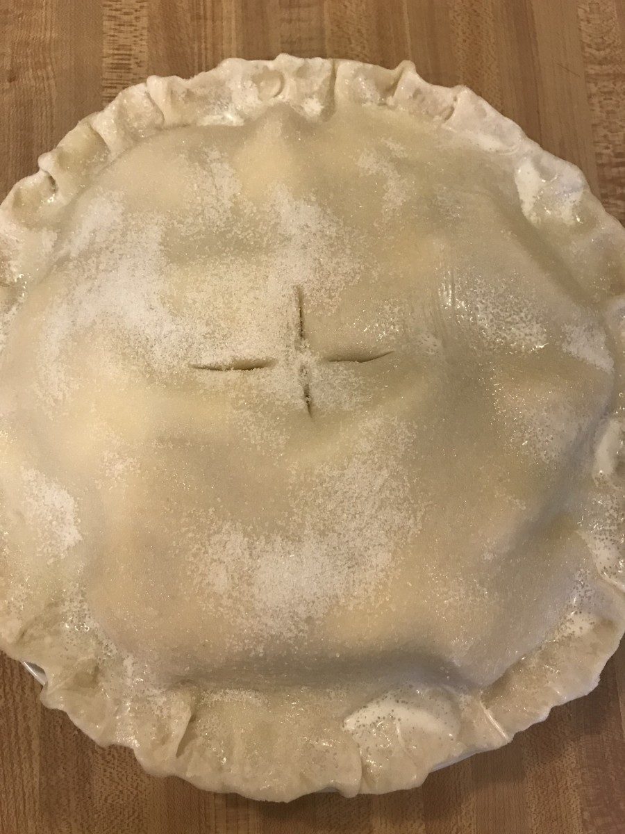 Brush the top crust with cream, sprinkle on the sugar then cut vents. Or you could prick the top with a fork. Granny would say to make it look like a little bird had hopped across the pie.