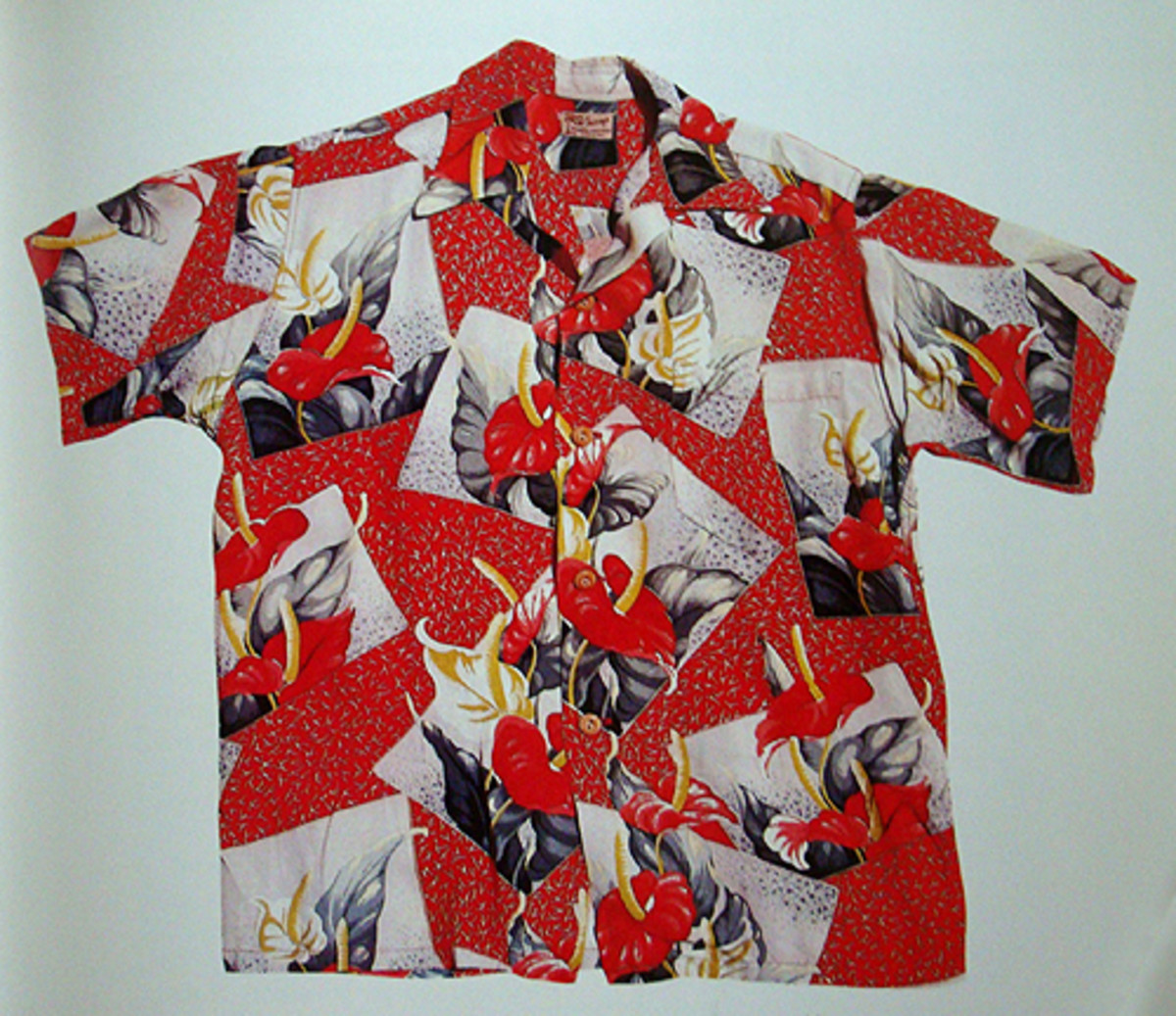 near perfect example of vintage shirt: wooden buttons, matched pocket, long collar, and bold pattern on hefty rayon. photo courtesy of Tommy Steele's Hawaiian Shirt Book.