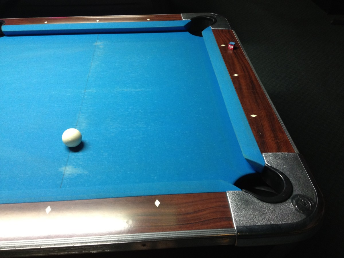 The second diamond is tough to see with the glare off the table, but the four balls are to the left of this photo. The cue ball is on the point where the imaginary lines described above intersect.