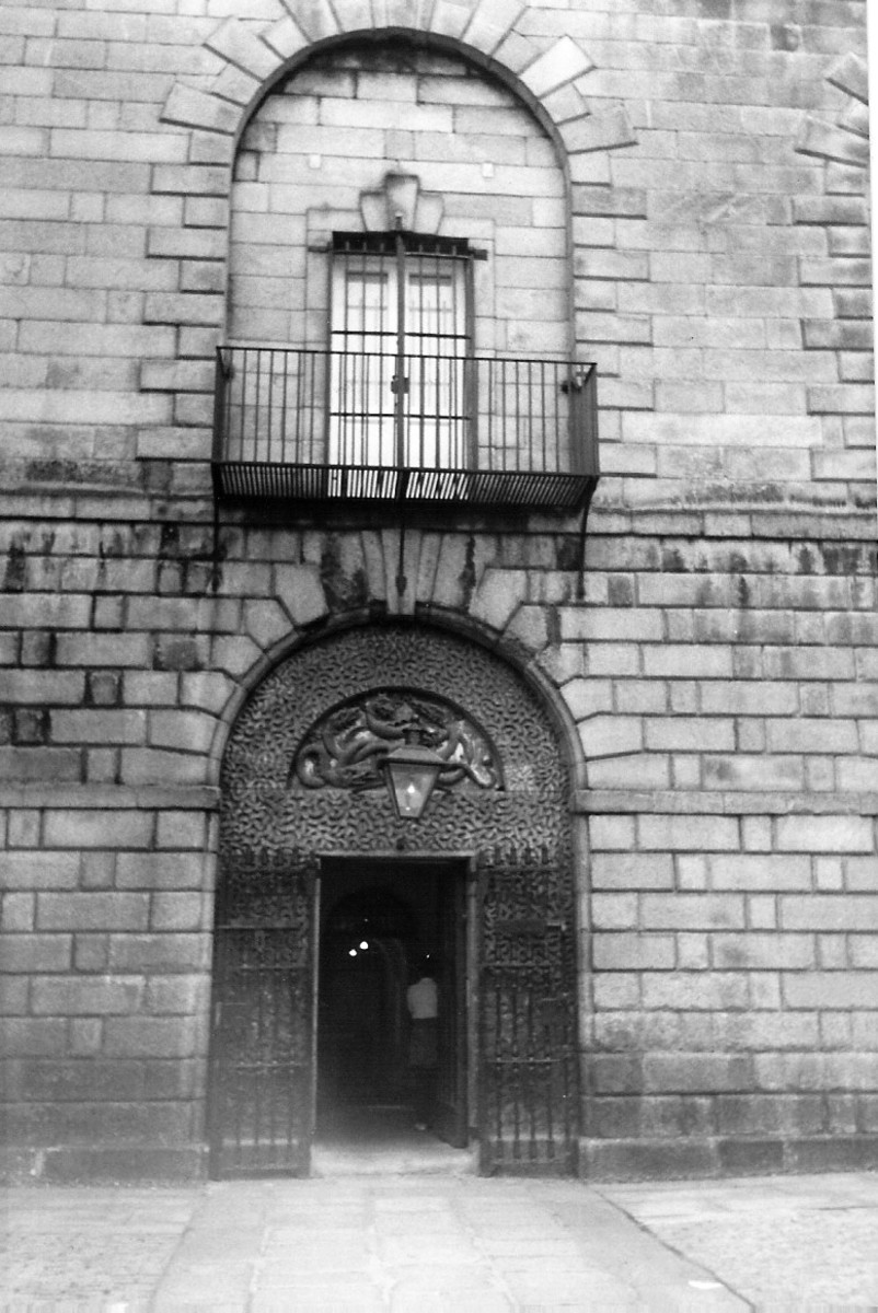 The rope is attached to the wooden stake above the doors and around the prisoners neck.   A lever opens the trap doors on the ledge and the prisoner falls to their death