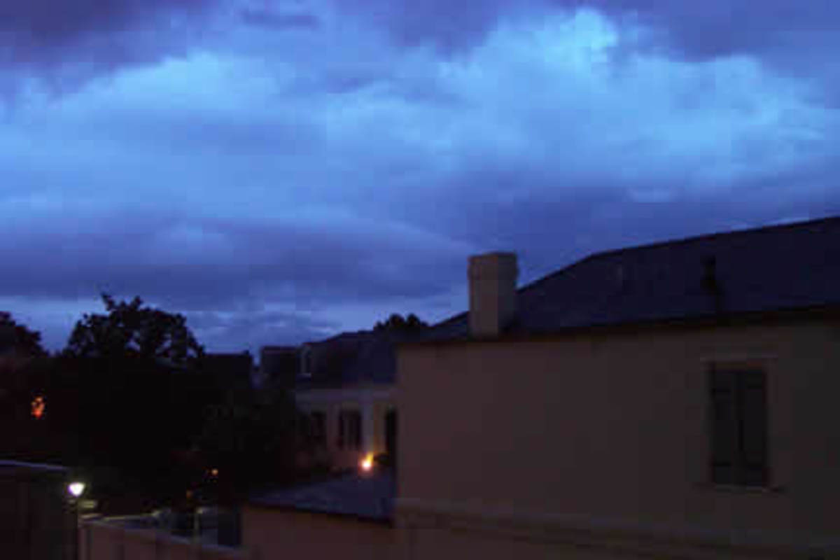 The view from the balcony with a storm coming in- the Convent is on the lower right, and the light is from the Beauregard-Keyes house. The Hotel Provincial is out of frame to the left and connected to the condos.