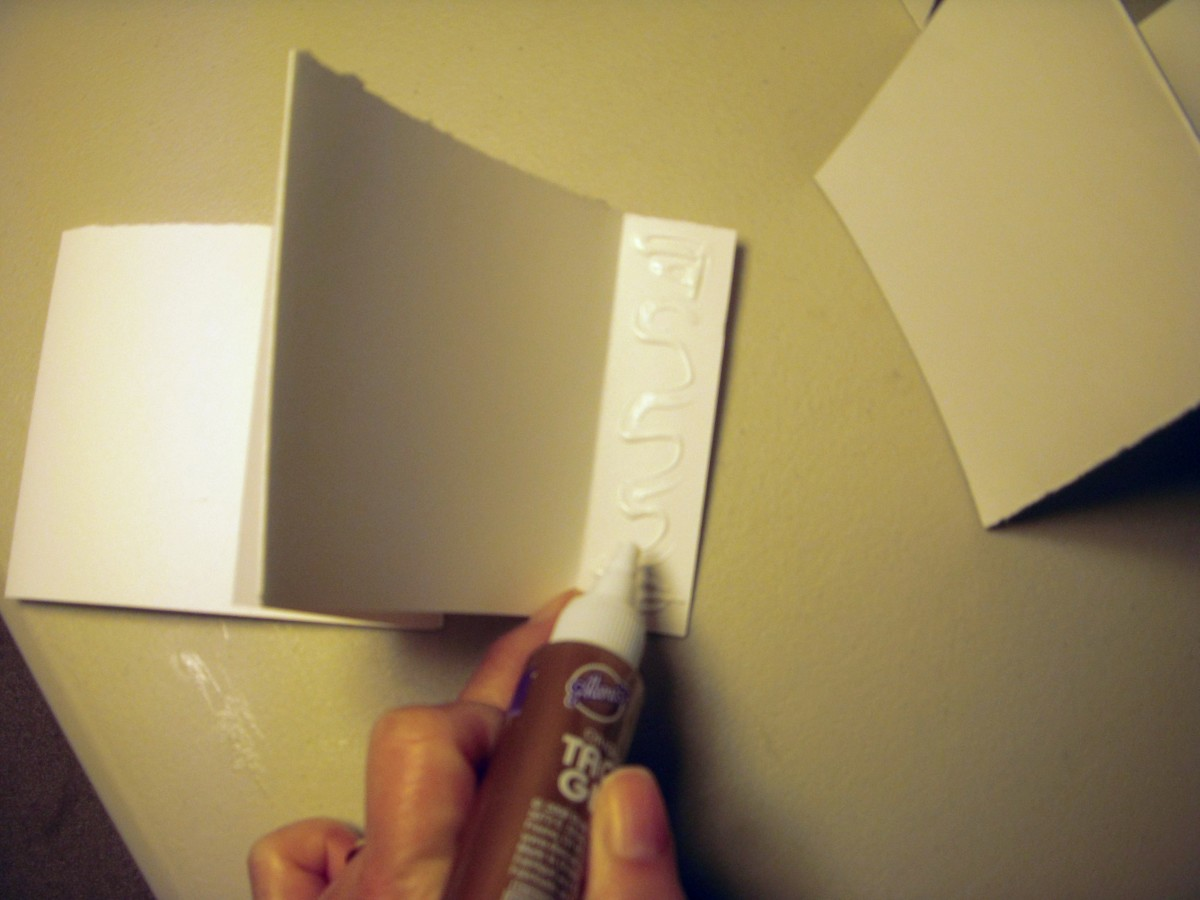Apply glue to short tab on one strip.