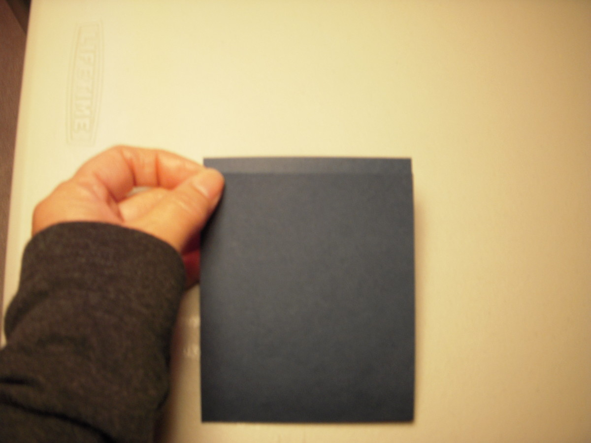 """Sharply fold the cardstock at the 4 1/8"""" mark and at the 4 3/8"""" mark to make the spine."""