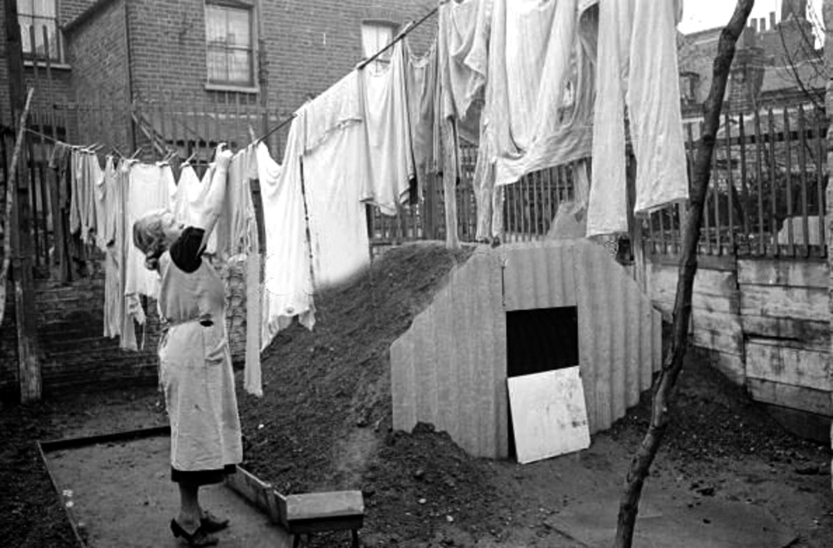 A woman hanging out her washing next to the new Anderson air raid shelter in her back yard.