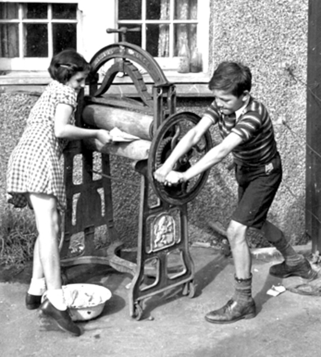 Mangling The Washing 13th September 1941: Peter and Pam putting washing through the mangle to wring it dry for their mother. Original Publication: Picture Post - 859 - The Life Of An Airman's Wife - pub. 1941 (Photo by Kurt Hutton / Picture Post / Ge