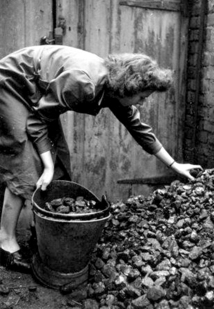 A home help fills a coal bucket with coal during a visit to the house of an invalid, so that there will be a plentiful supply of fuel within easy reach.