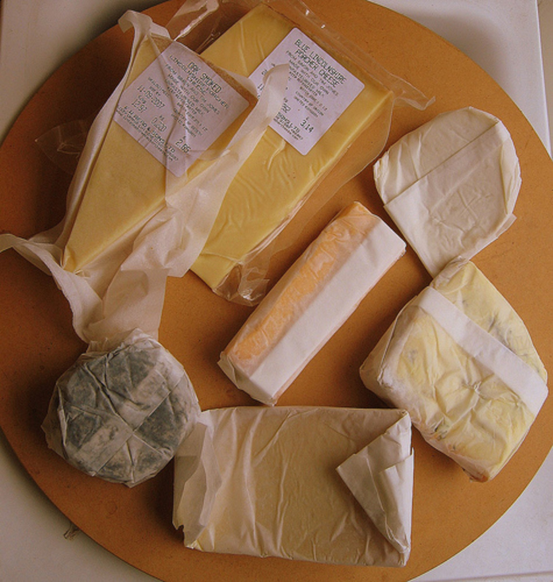 Wrap cheeses in cheese paper, parchment paper, or waxed paper.