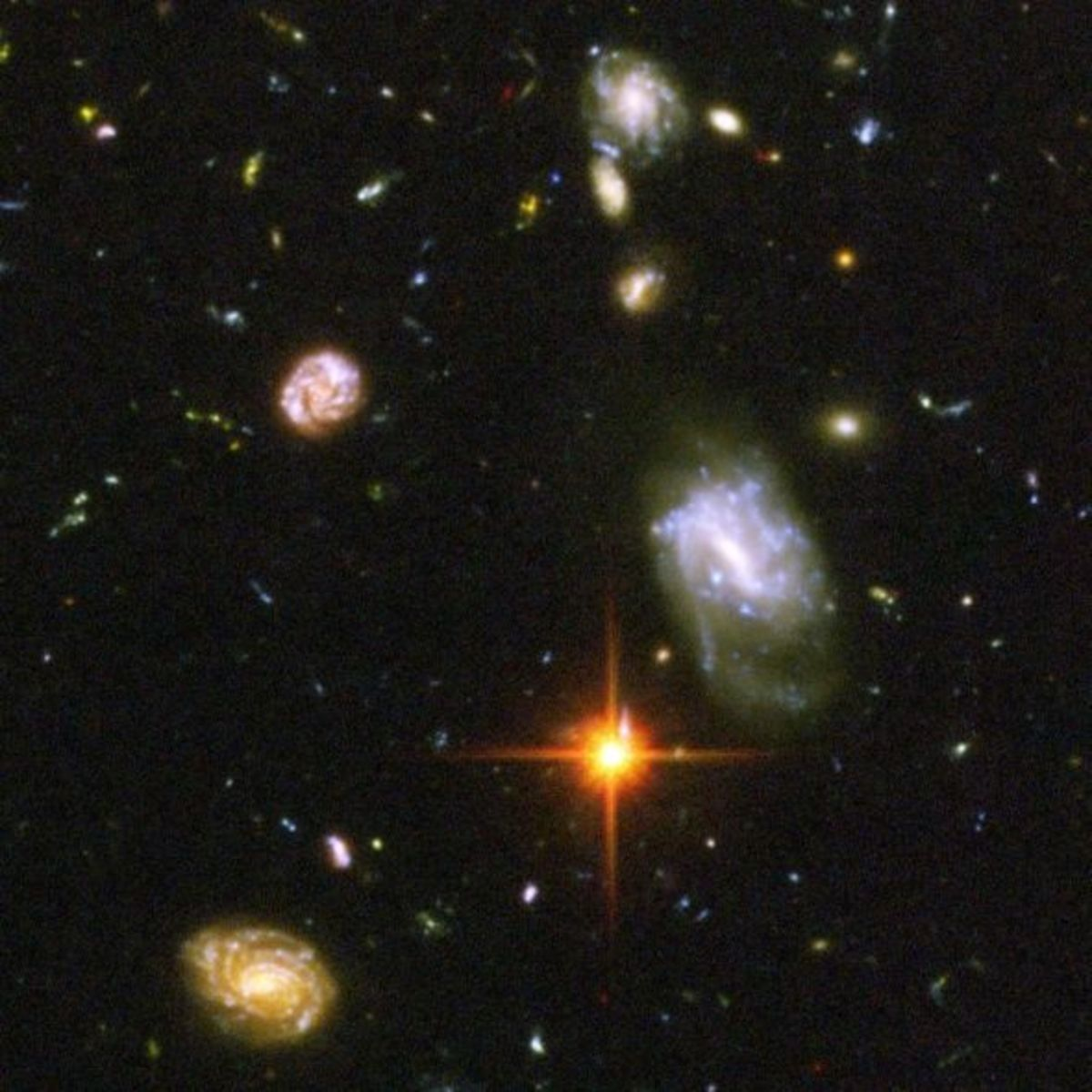 Many far-away galaxies and one foreground star from our own Milky Way.