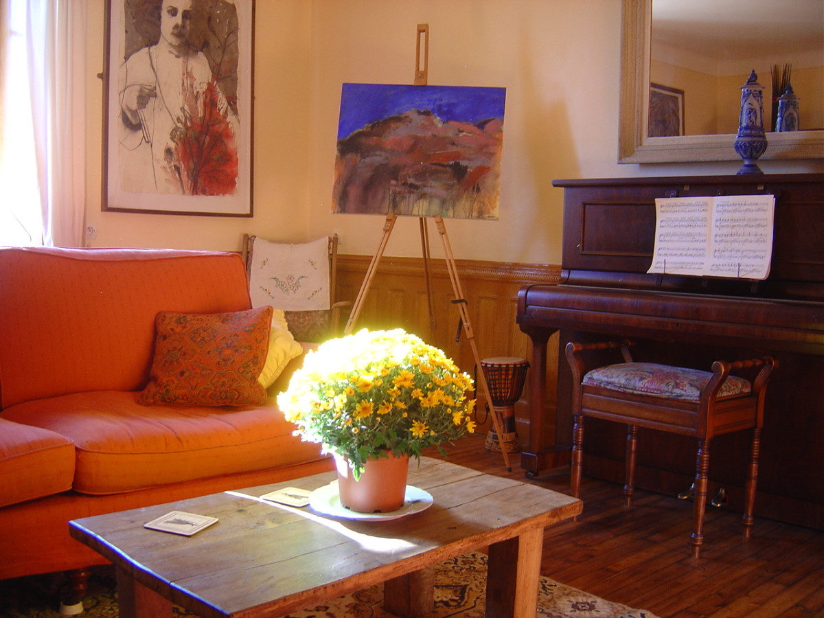 There is a piano in the sunny sitting room