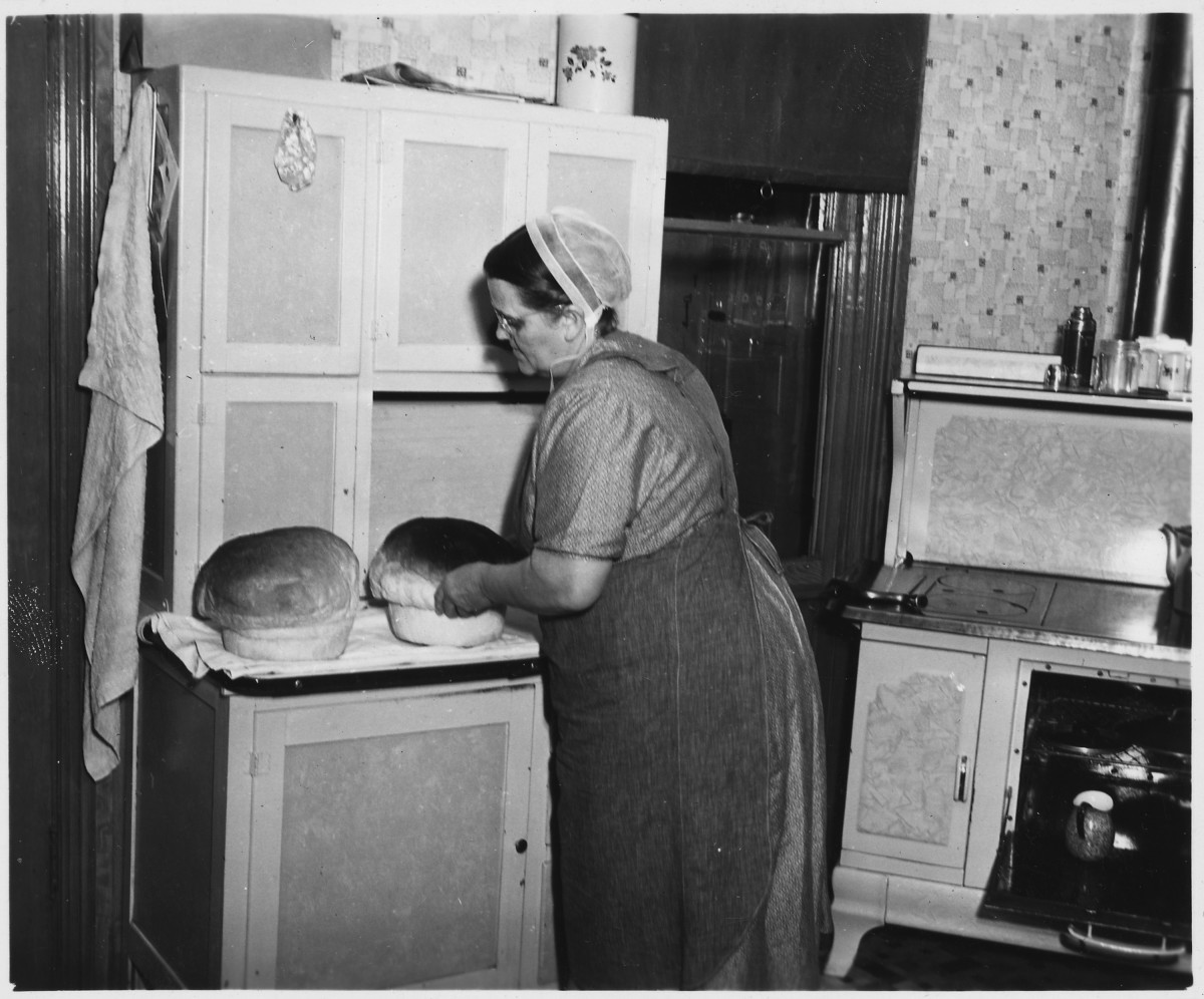 Amish housewife baking bread in her kitchen.