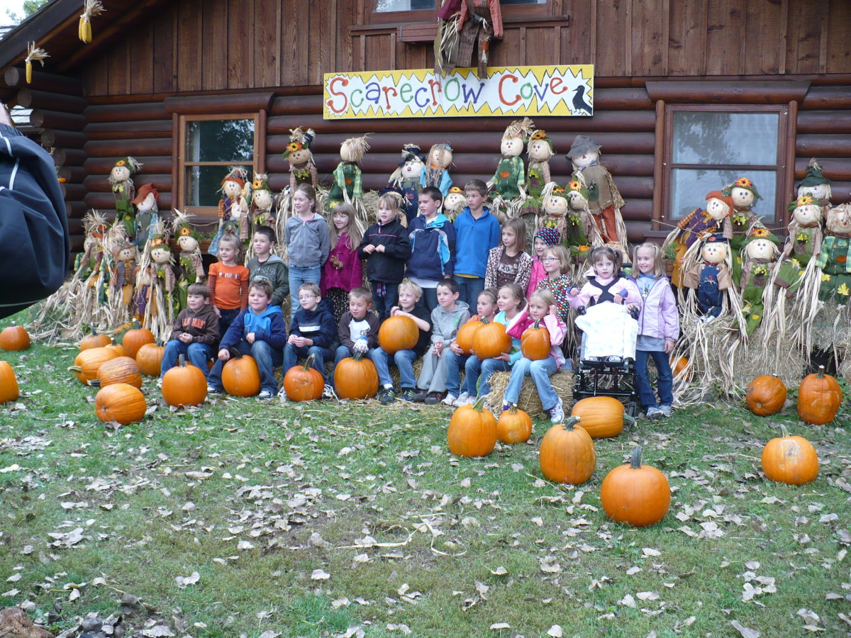 A classroom gets their photo taken in front of Scarecrow Cove during their field trip to the Papa's Pumpkin Patch