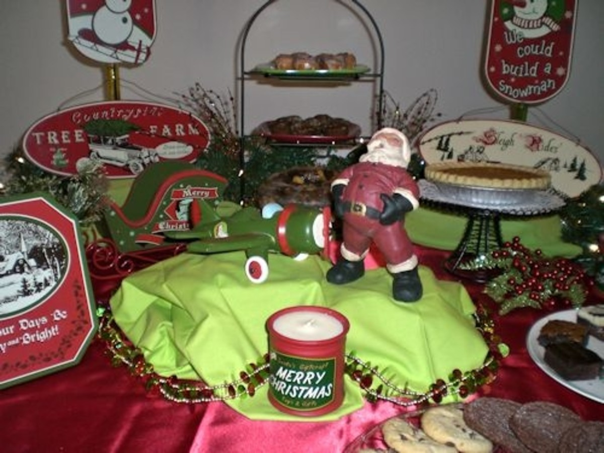 "In the center of the table is the retro airplane, Santa and a ""Merry Christmas"" candle. The are stair-stepped with boxes covered in vintage green fabric."