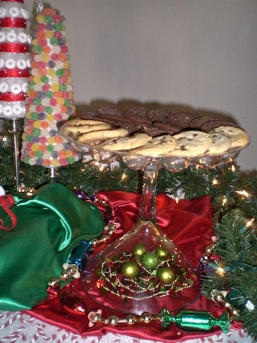 The cookie platter is set atop an oversized martini glass turned upside down. Beaded garland and small ornaments are placed under the bowl portion of the upside down martini glass.
