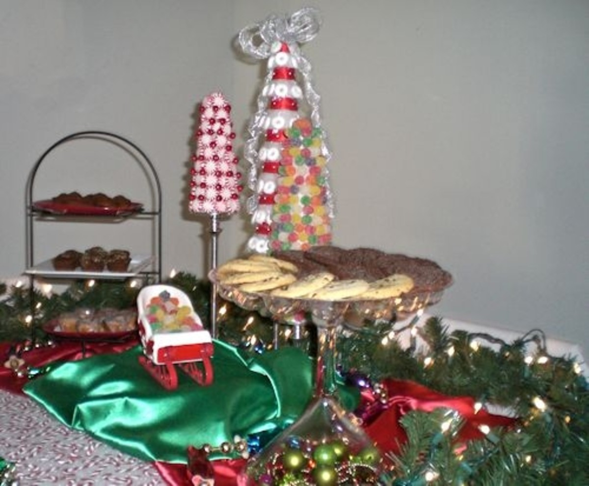 The tiered buffet stand holds assorted bite size treats on red and white plates.