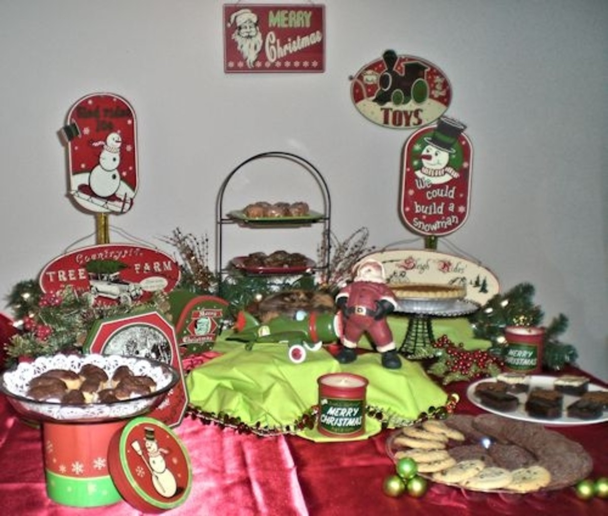 The decor for this buffet includes vintage metal signs of different shapes and sizes, lighted evergreen garland, retro style gift box, airplane, Santa and sleigh.