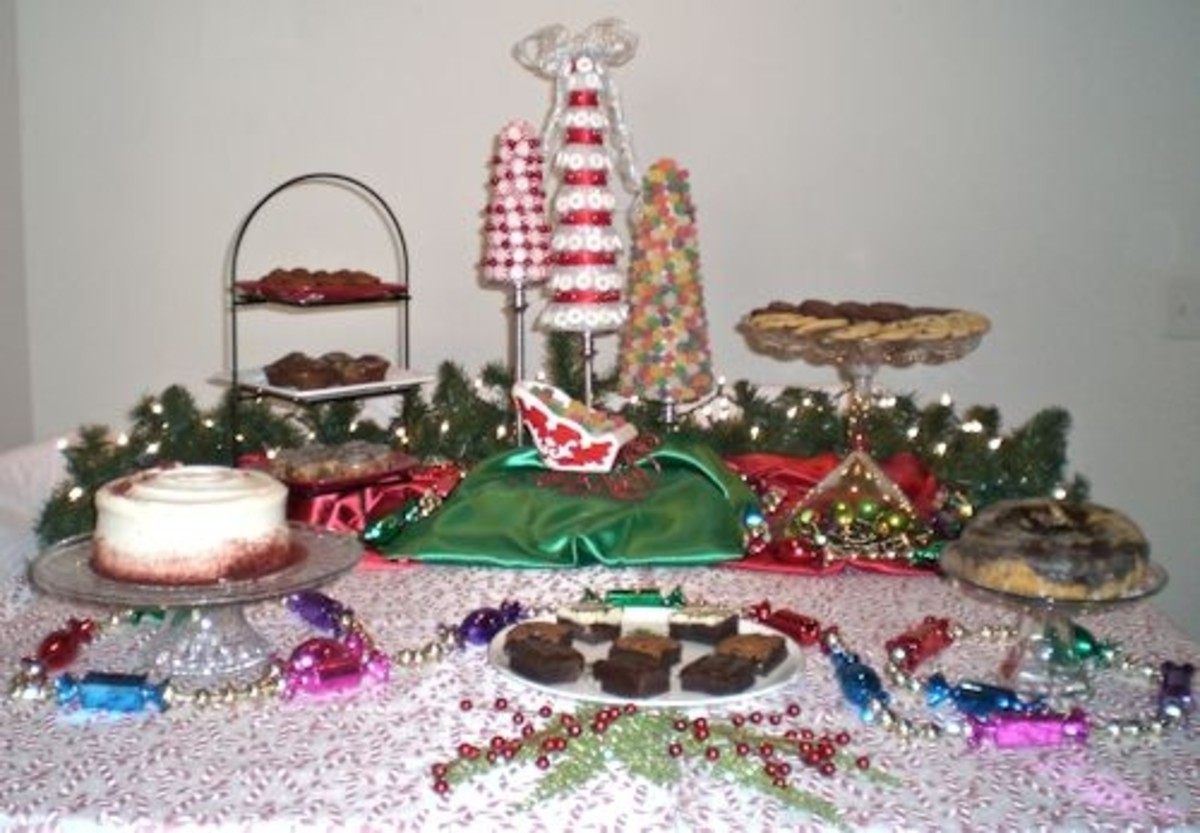 The decor used for this buffet includes wrapped candy garland, lighted evergreen garland, red, green and candy cane fabrics, ornaments, a sleigh and candy Christmas trees.