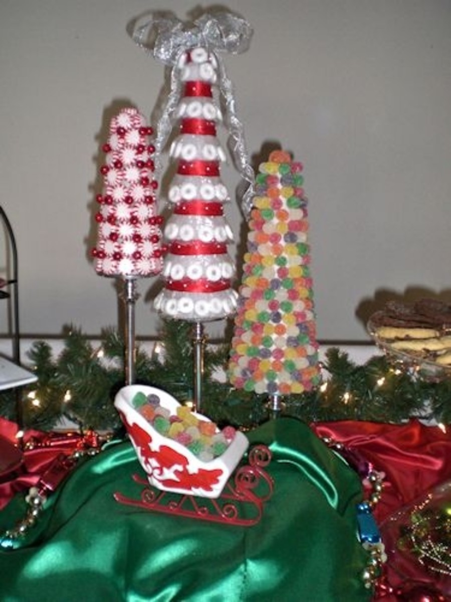 There are 3 candy Christmas. One is made of peppermint candies and wired berries. The second is made of wintergreen Lifesaver candies and red and white ribbon. The last is made of spice drops (gum drops). They are each displayed on silver pedestal ca