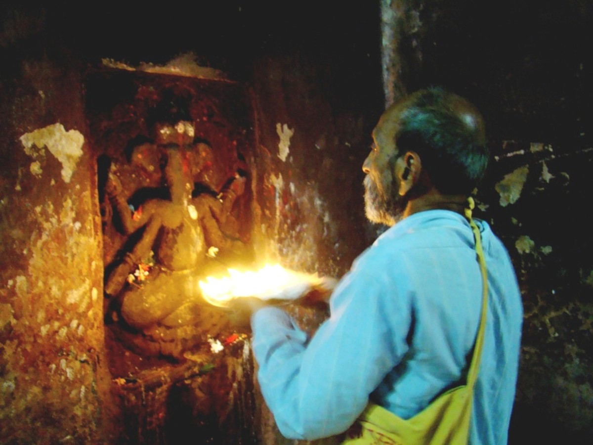 A devotee performing AARTI with lighted lamps