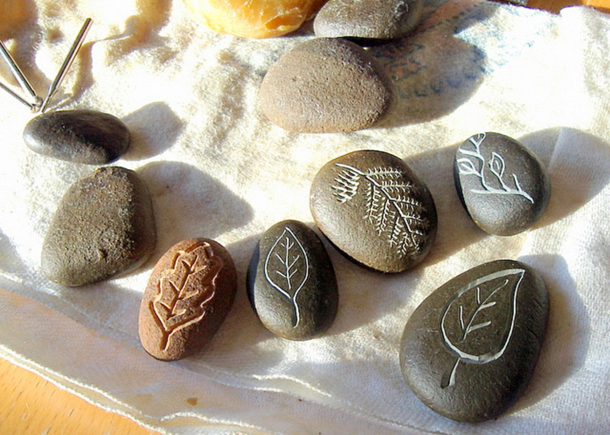 These beach pebbles were carved under running water using diamond bits in a Dremel tool, then beeswax was rubbed onto them to make the carvings more distinct.