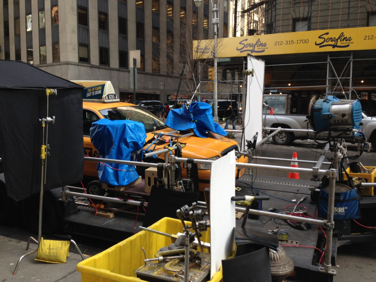 """A New York City taxicab loaded onto a ""process trailer"" with lights and cameras in preparation for a filming . . . """