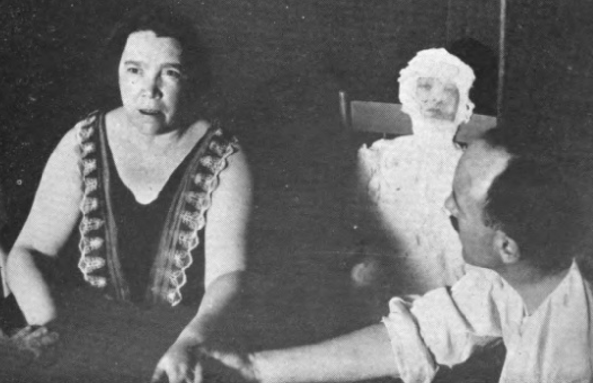 medium Mary Marshall with an alleged ectoplasm form of a woman (obviously using a cut out photograph of a face).