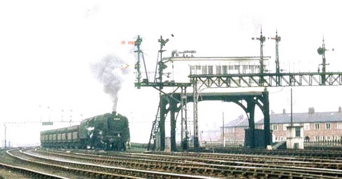 Box on stilts :9F 2-10-0 and Iron Ore bogies from Tyne Dock for Consett pass Green Lane near Washington, Co. Durham. Note the signal gantry and long twin bracket this side of the elevated box.