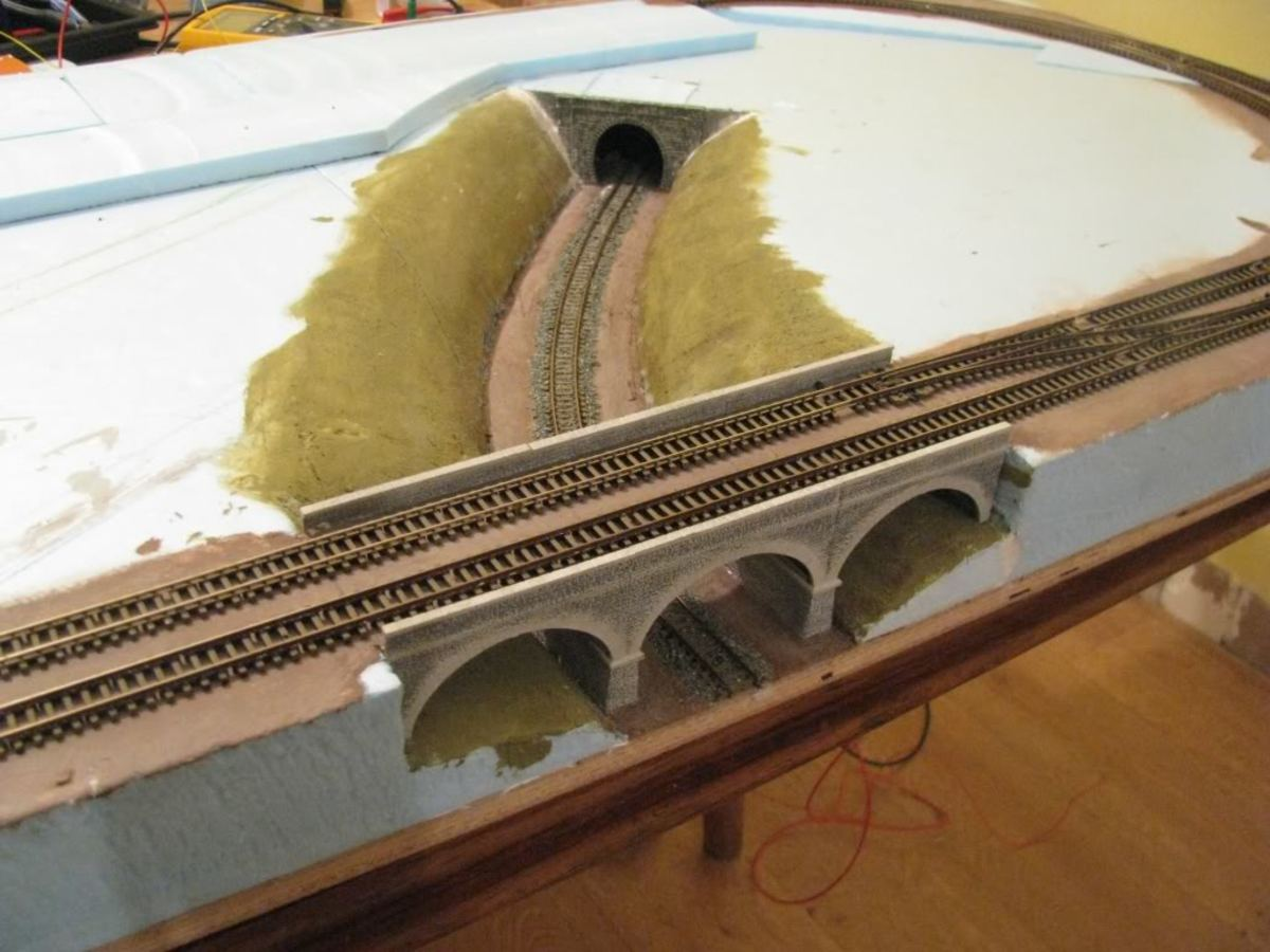 Embed the viaduct, get the railway done first, surroundings later. You'll have picked up a few tips by the time you've got that far, changed your mind or turn it into plain fields with hedging. Choices are infinite, tractors, combines, livestock...