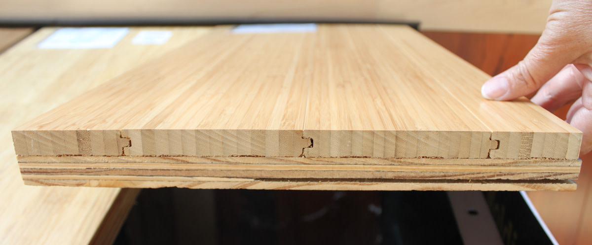 This is the edge of a flooring sample of solid vertical bamboo mounted on a piece of plywood.