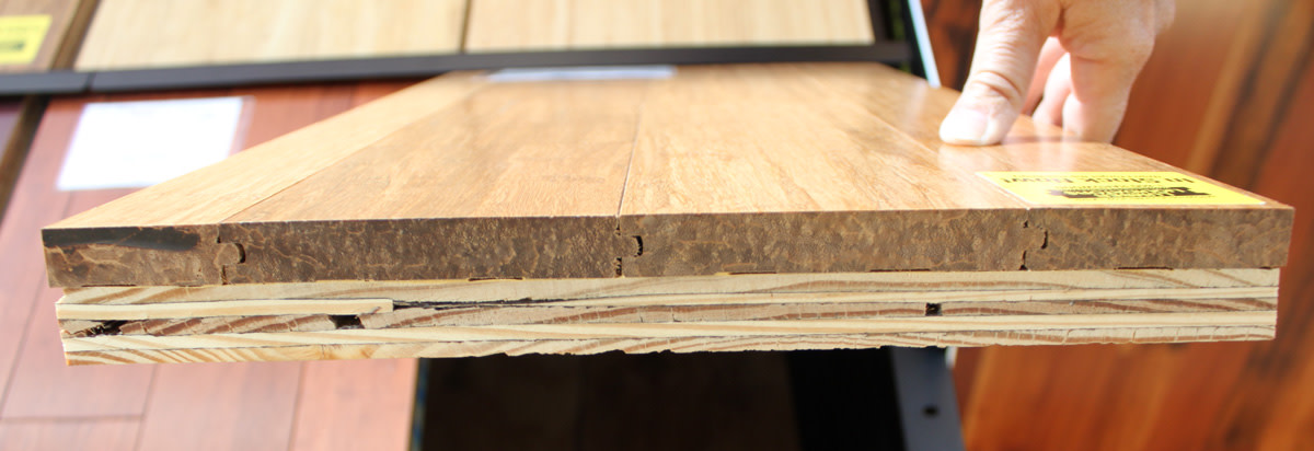 This is the edge of a flooring sample of solid strand bamboo mounted on a piece of plywood.