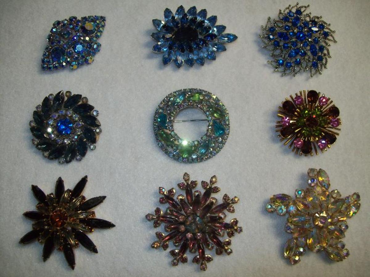 Colorful rhinestone pins. The round one in the middle is a Weiss.