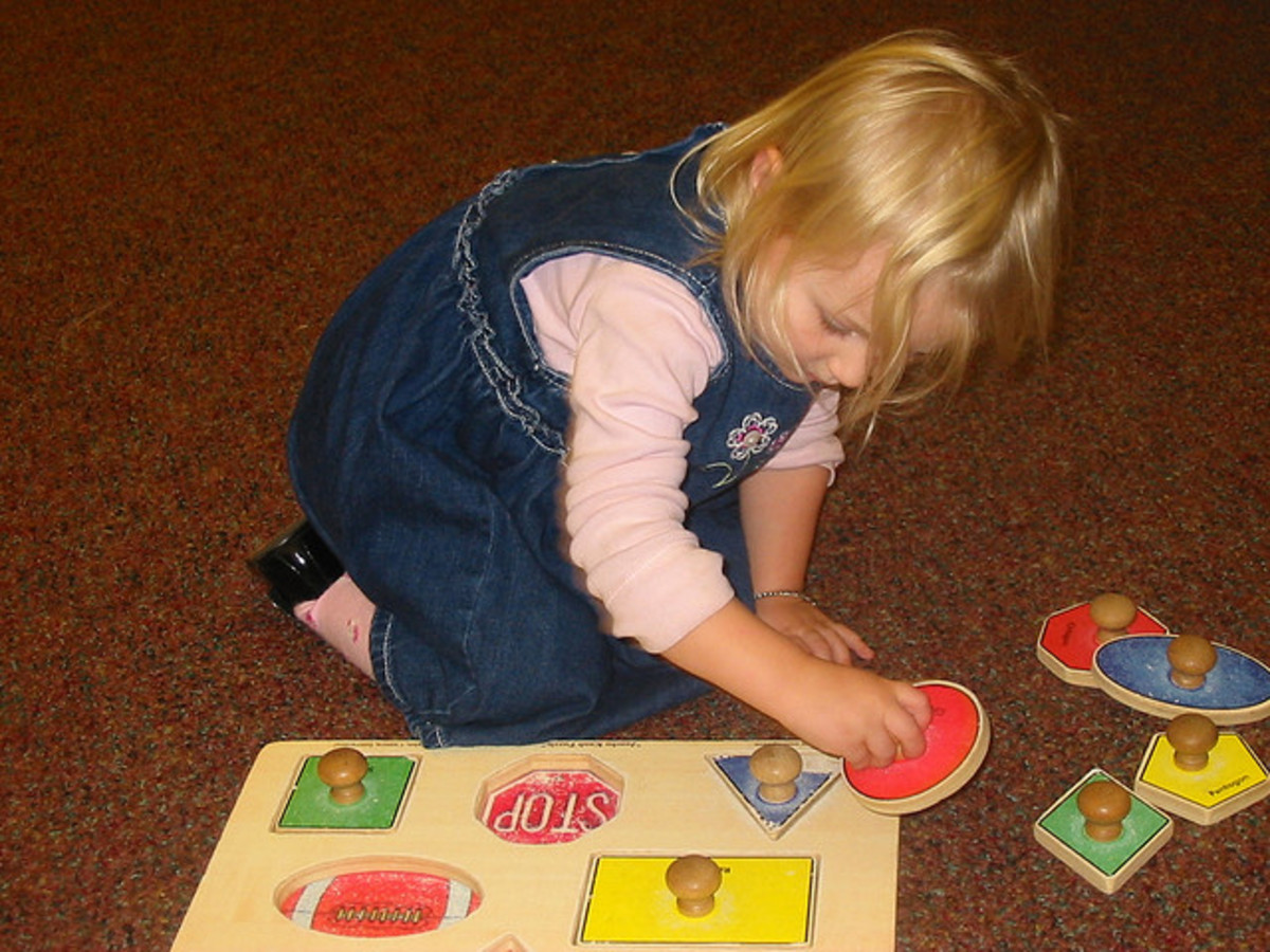 Child playing with shape puzzle with knobs. Large pieces and good contrast with colored pieces and light colored background.