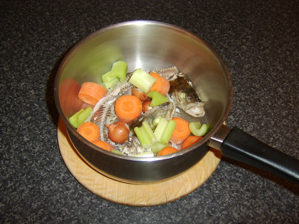 The fish heads and bones are added to a large soup or stock pot with the principal vegetable ingredients for the stock