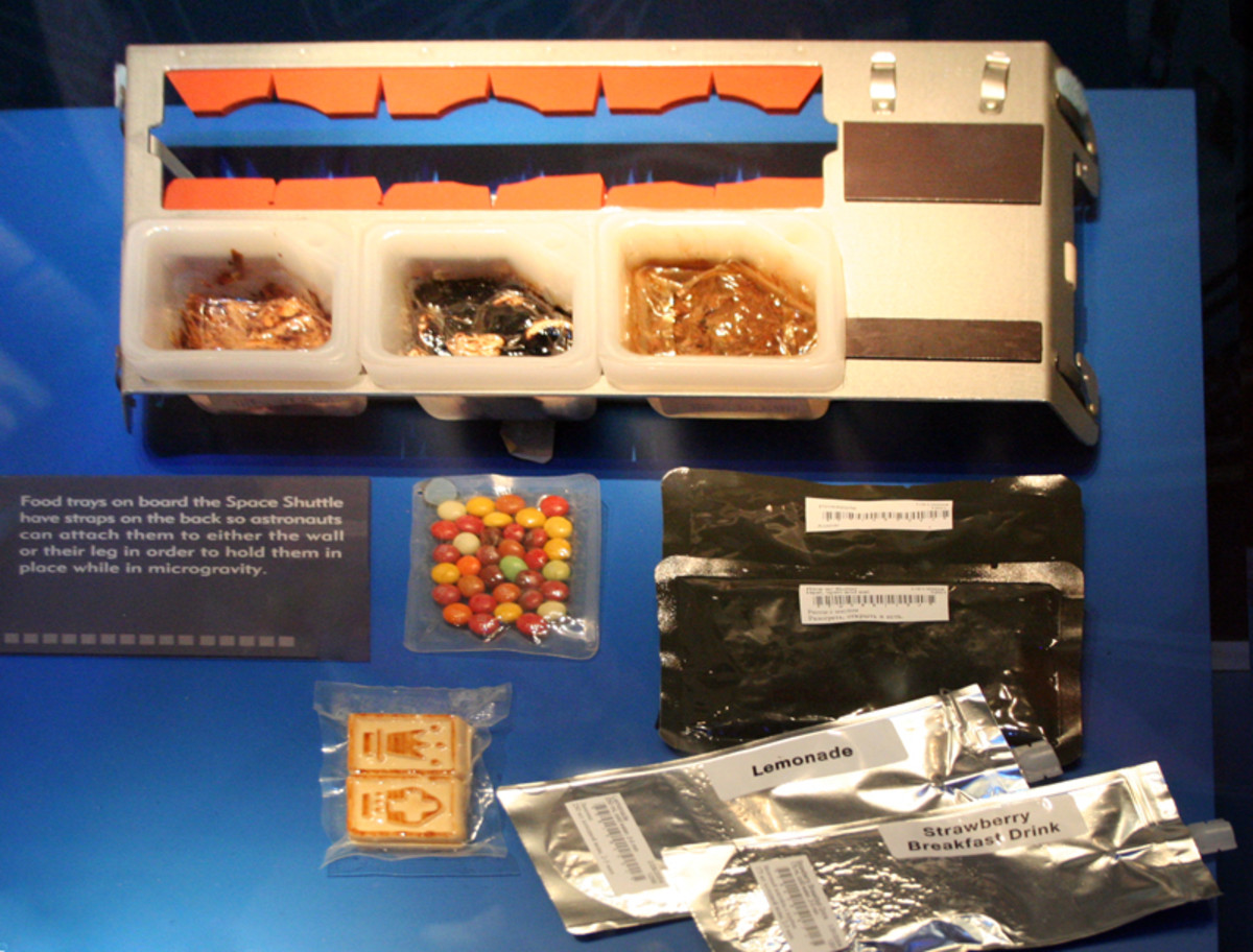 Food Tray, with dried drinks and other foods beside it. This tray would be strapped to a wall or the astronaut leg for consumption.