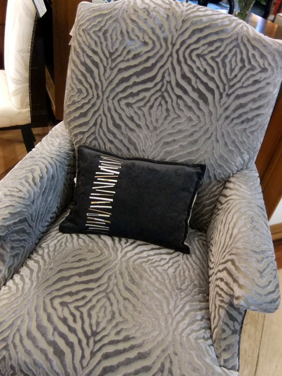 11. A black colored throw cushion with white and gray pattern, to pick up the main color of the armchair