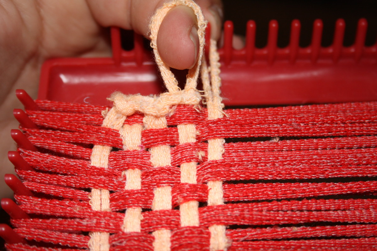 The first step to sealing the edges of a potholder, grab the end of a loop and pull it off the loom making sure to hold on to the loop