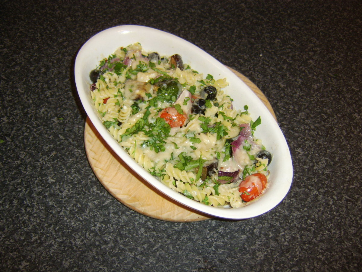 Fusilli pasta is stirred through a selection of roasted vegetables and topped with parmesan cheese