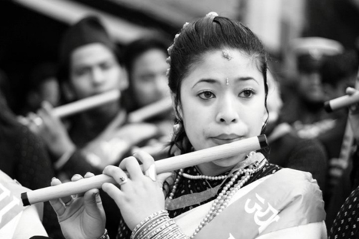 Nepali girl from Newar ethnic group playing Flute in a Newari event.