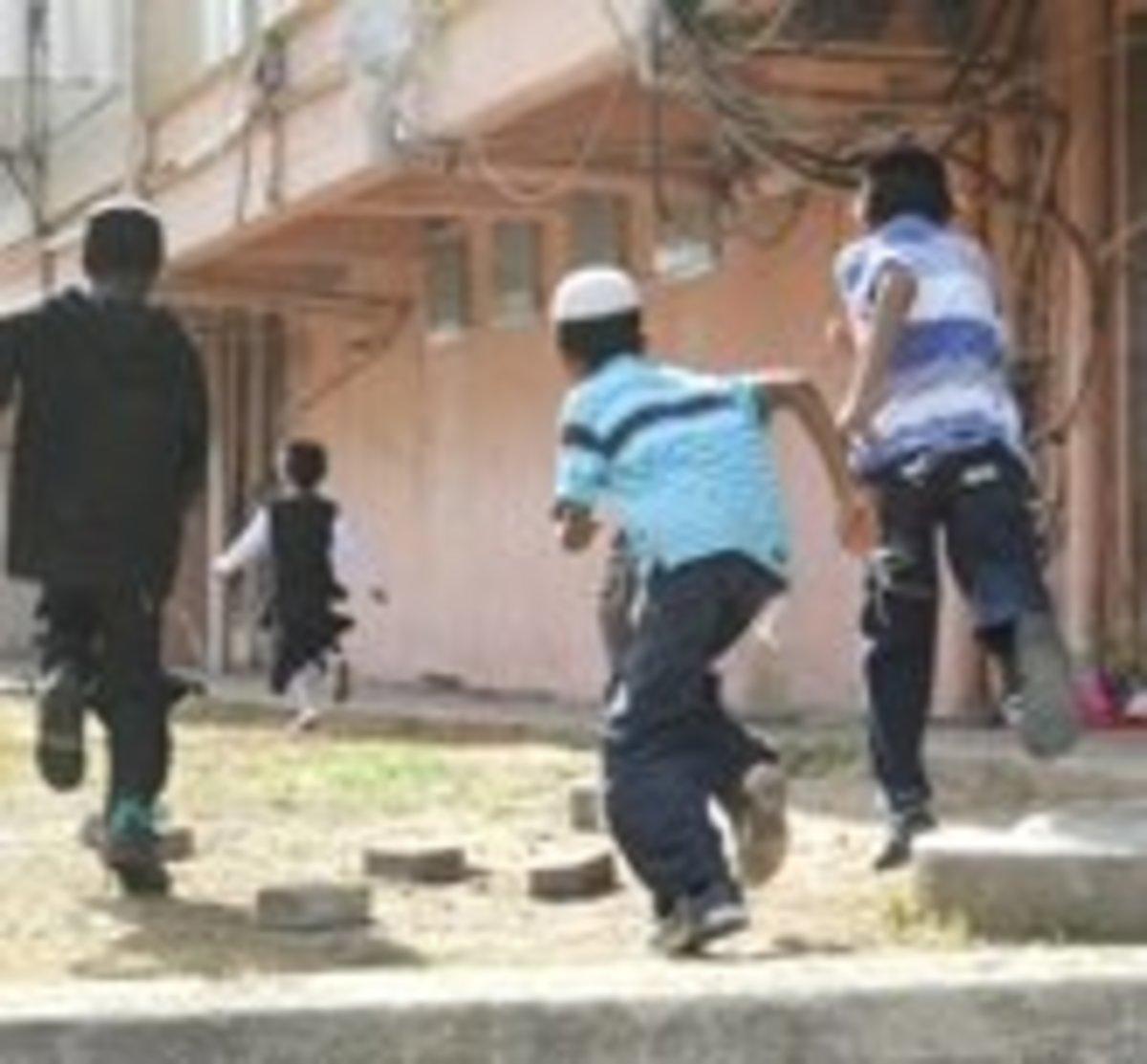Israeli children running to bomb shelter when air raid siren is sounded.