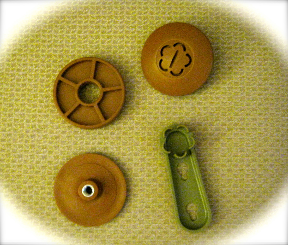Parts included, clockwise from top left:  spacers; top cap; magic wrench; bottom cap.