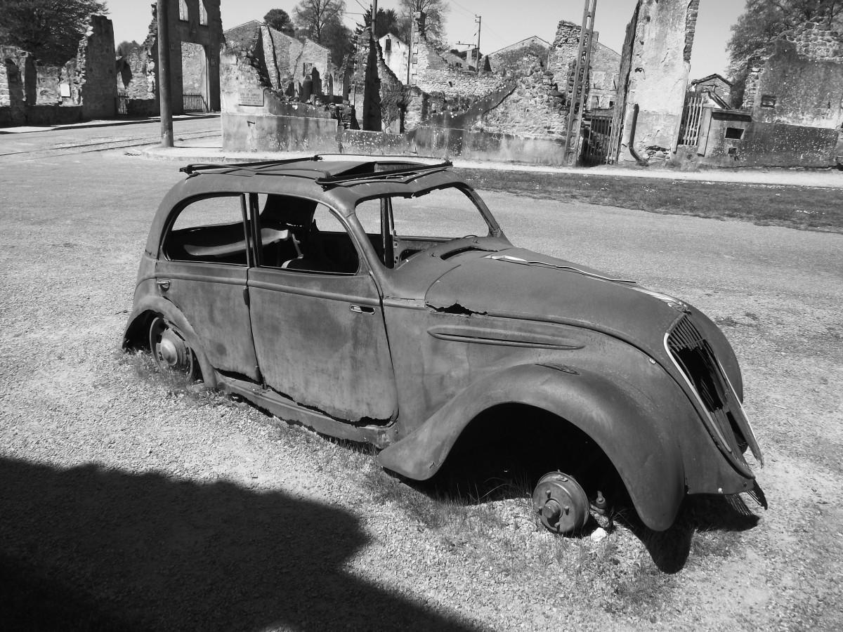 Oradour-sur-Glane. Rusted Citroen car and ruins.