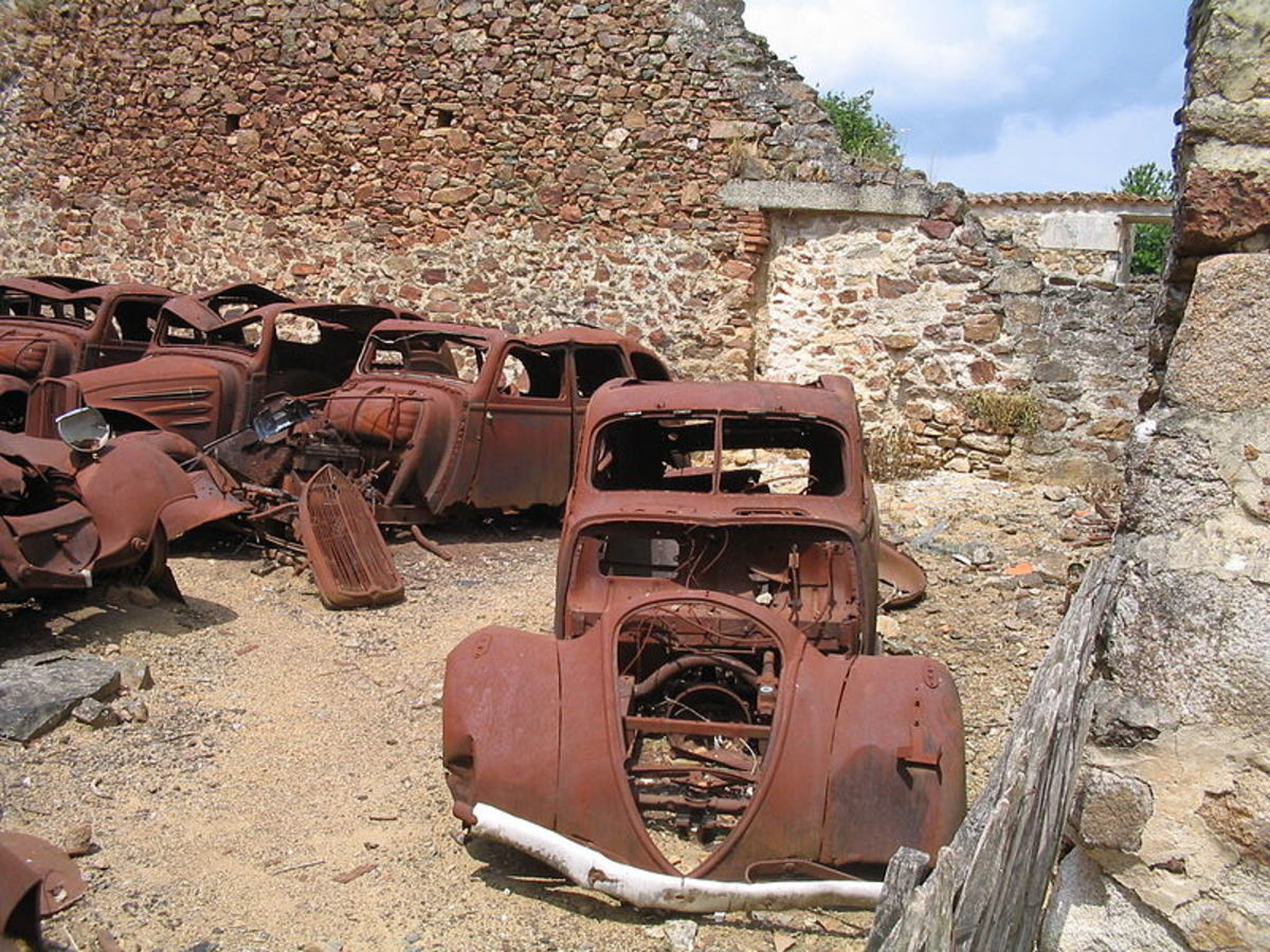 Rusted cars in a ruined building, Oradour-sur-Glane.