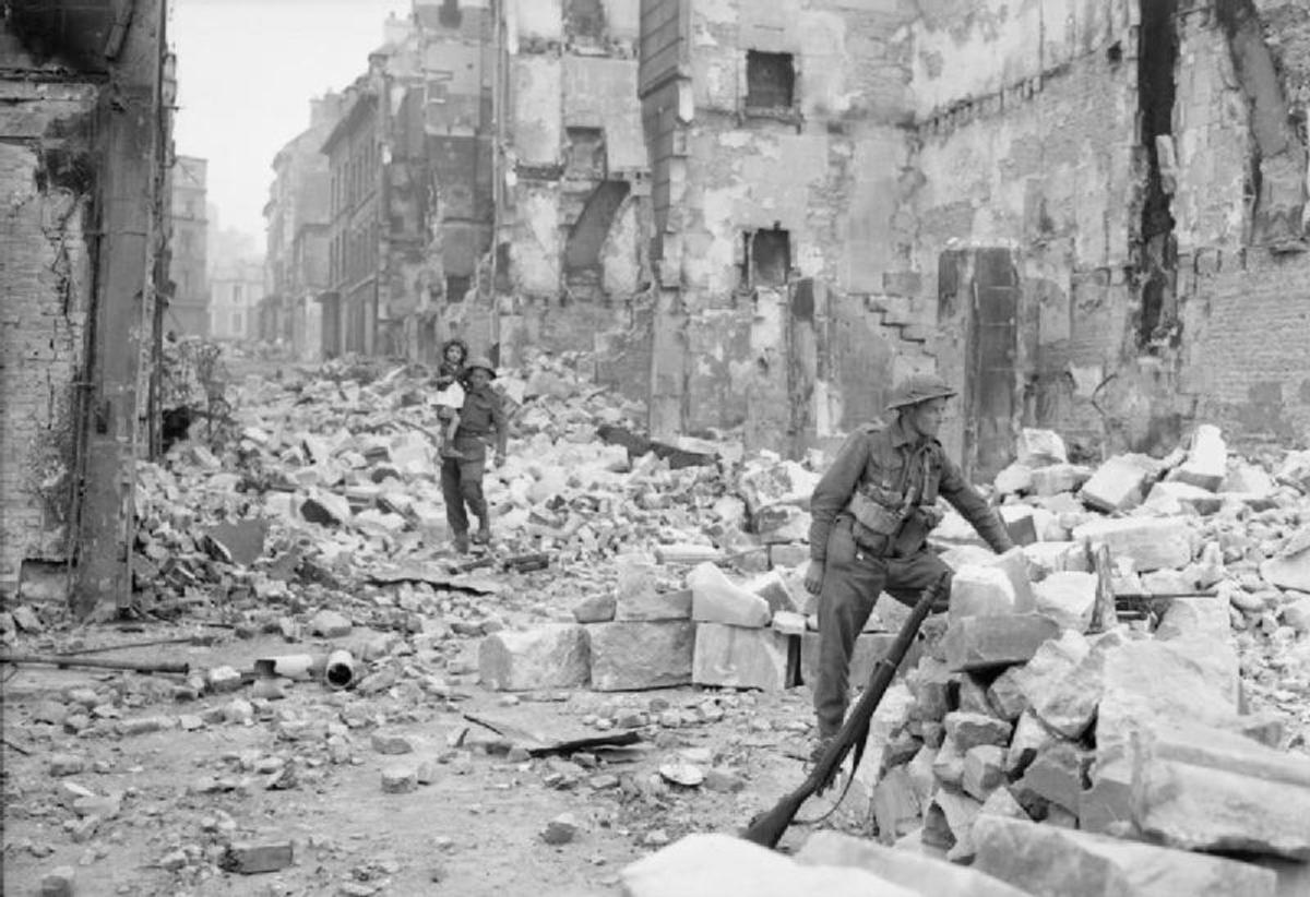 A British soldier rescues a French girl in a ruined city, WW2, summer 1944.