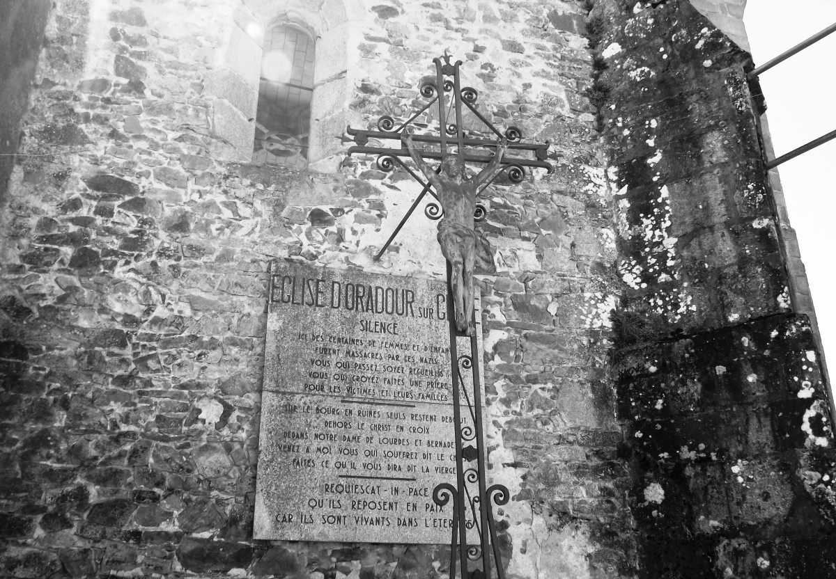 Figure of Christ and remembrance plaque outside Oradour church.