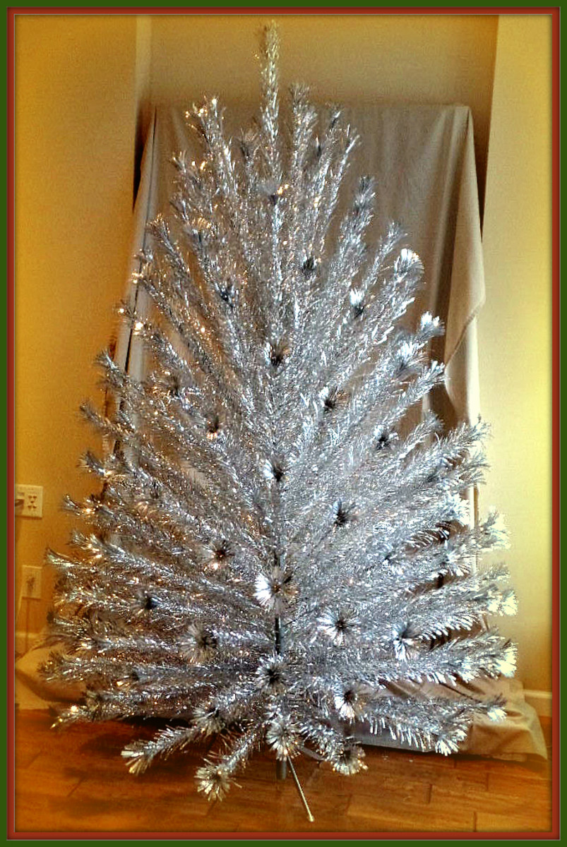 Early 1960s Peco Seven foot Aluminum Christmas Tree with 151 Pom Pom end branches. Very good used condition; complete with all 151 branches, 151 paper sleeves, two trunk poles, pole joining pin, & metal stand.