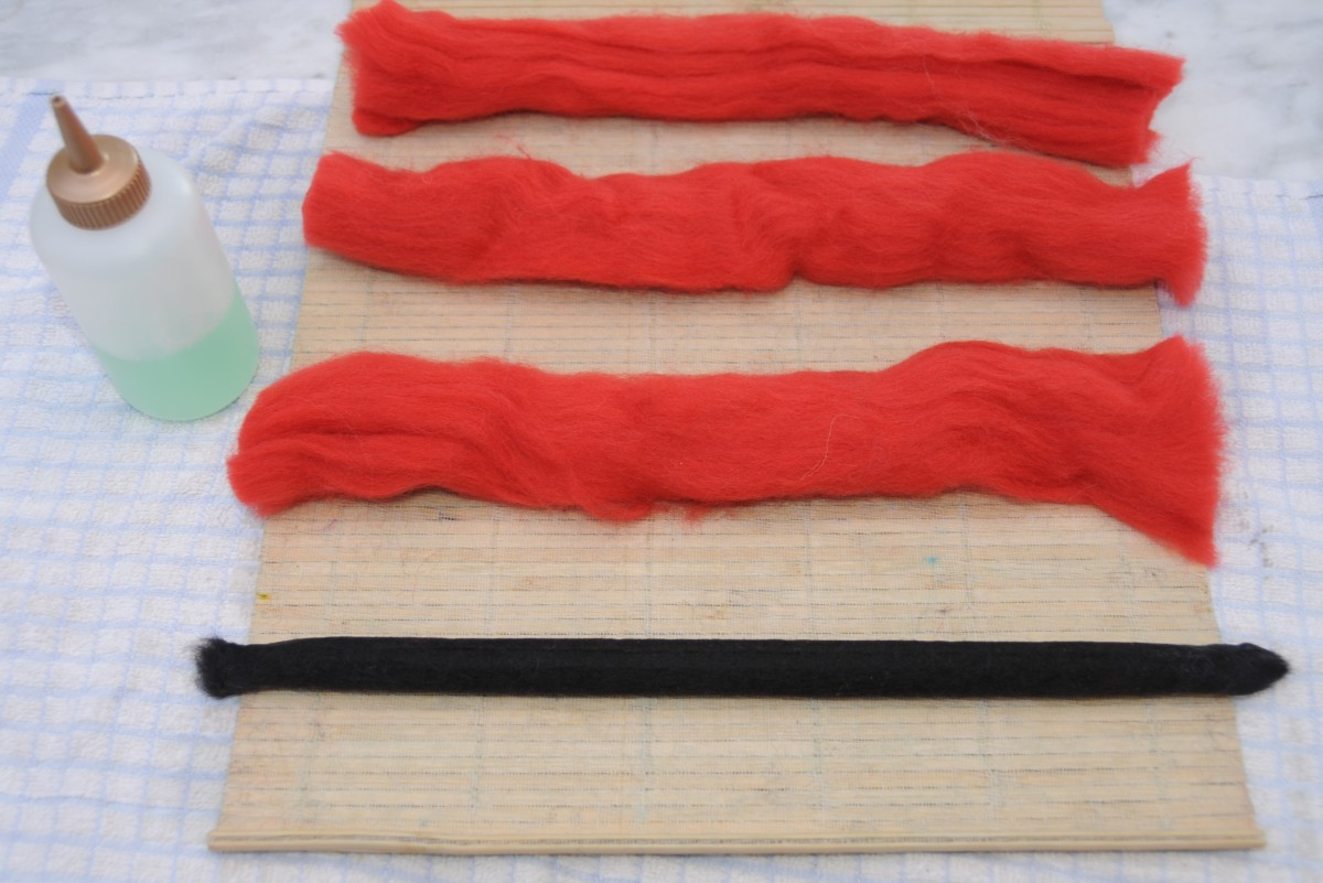 Two black layers felted and lying alongside three layers of red wool roving